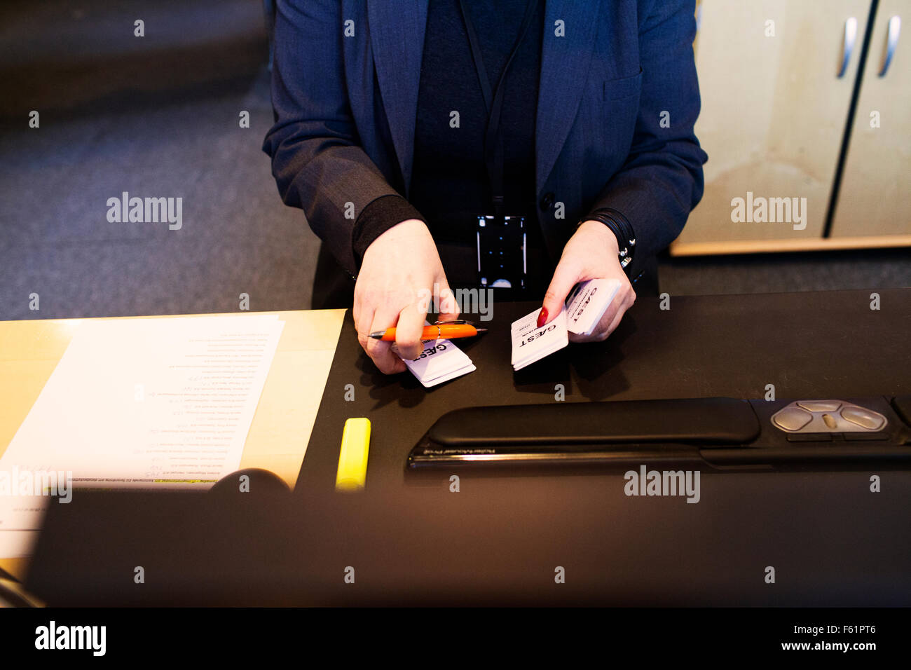 Receptionist holding name tags for visitors - Stock Image