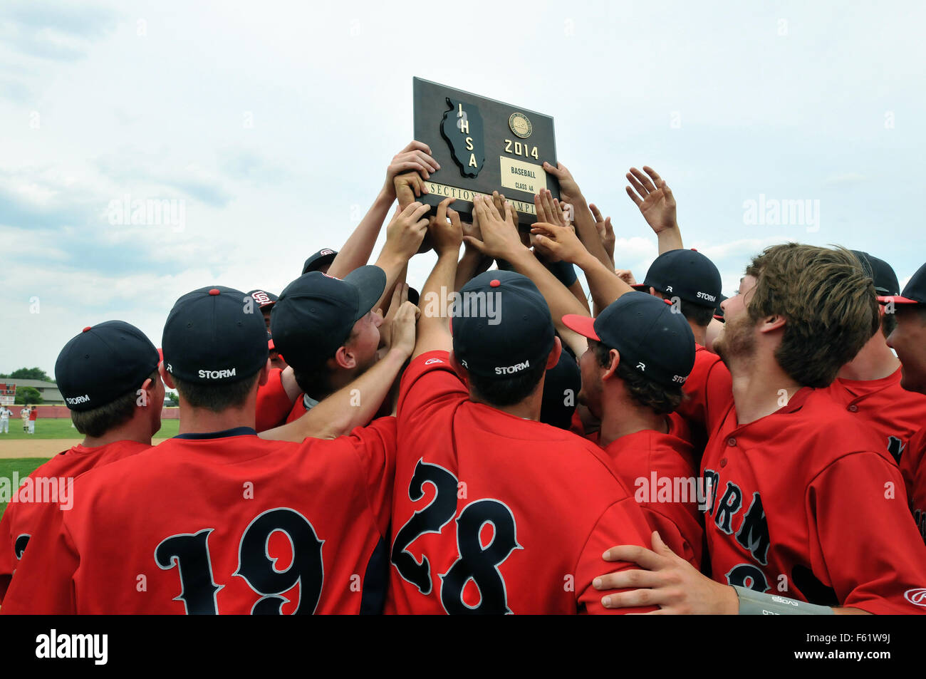 Players all reach to touch a championship title plaque they had just earned in winning a high school sectional playoff - Stock Image