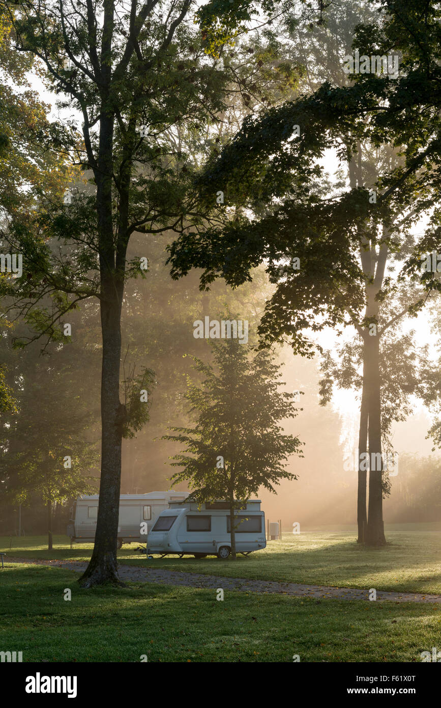 A campsite and caravan in the mist at dawn in France - Stock Image