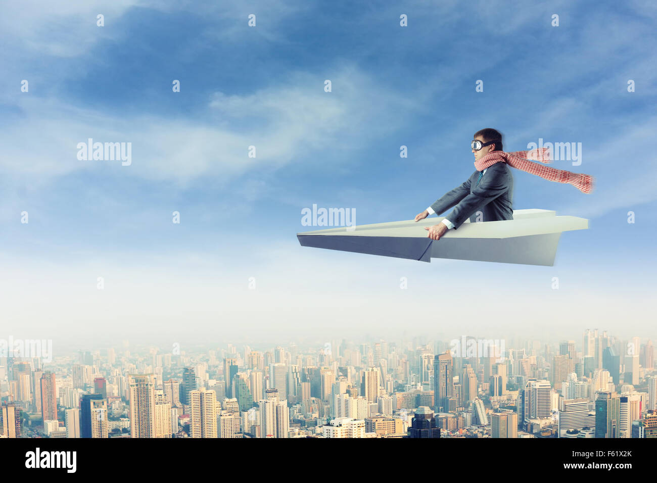 Businessman with the scarf on paper airplane above the city - Stock Image