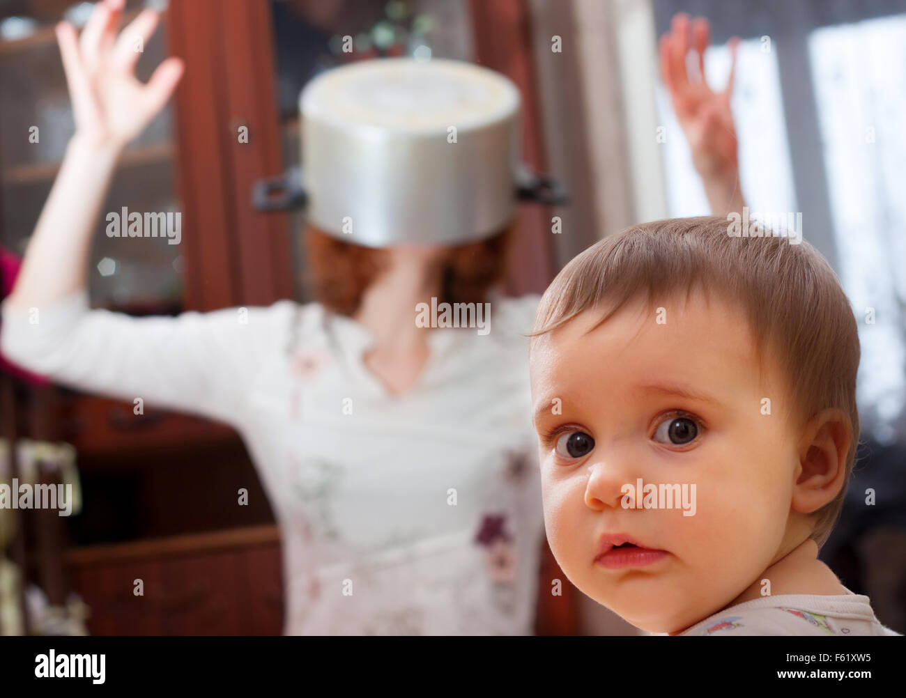Portrait of scared baby against crazy mother with pan on head - Stock Image