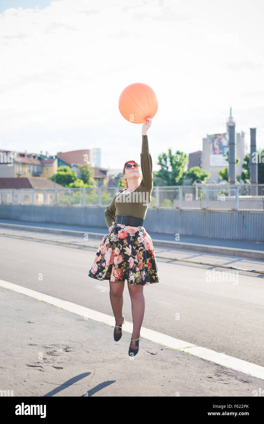 young handsome caucasian redhead woman jumping, playing with orange balloon, hand on her hips, looking up - youth, - Stock Image