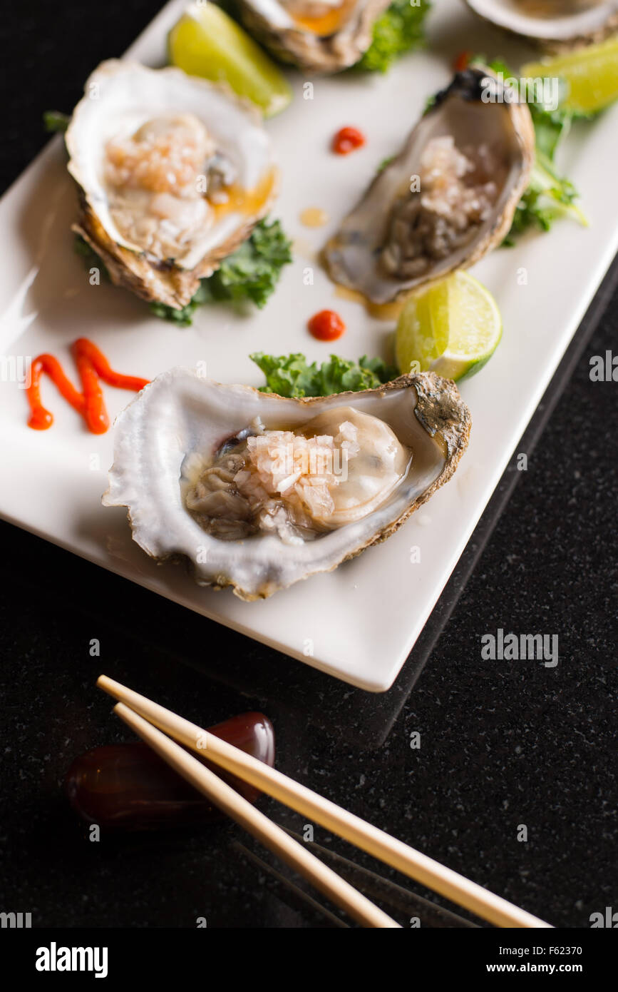Angled view of oysters on the half-shell on a rectangular plate with chopsticks. Stock Photo