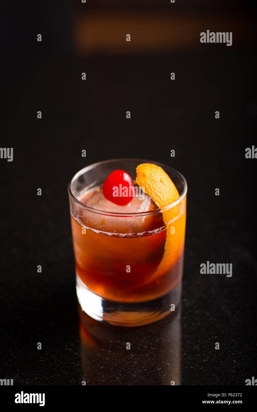 Old-fashioned cocktail on with a dark background. - Stock Image