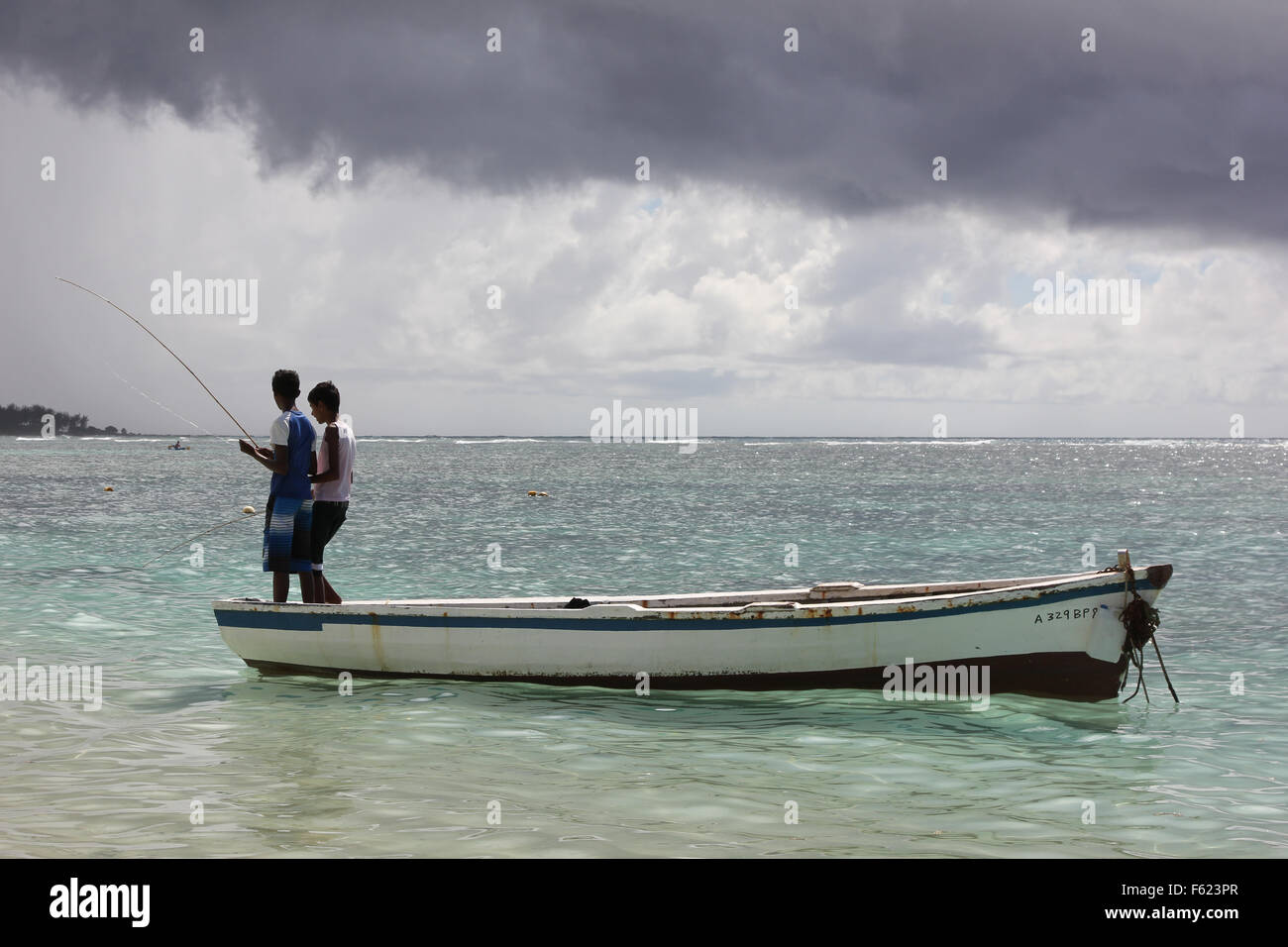 Two African boys are fishing on a boat. Stock Photo
