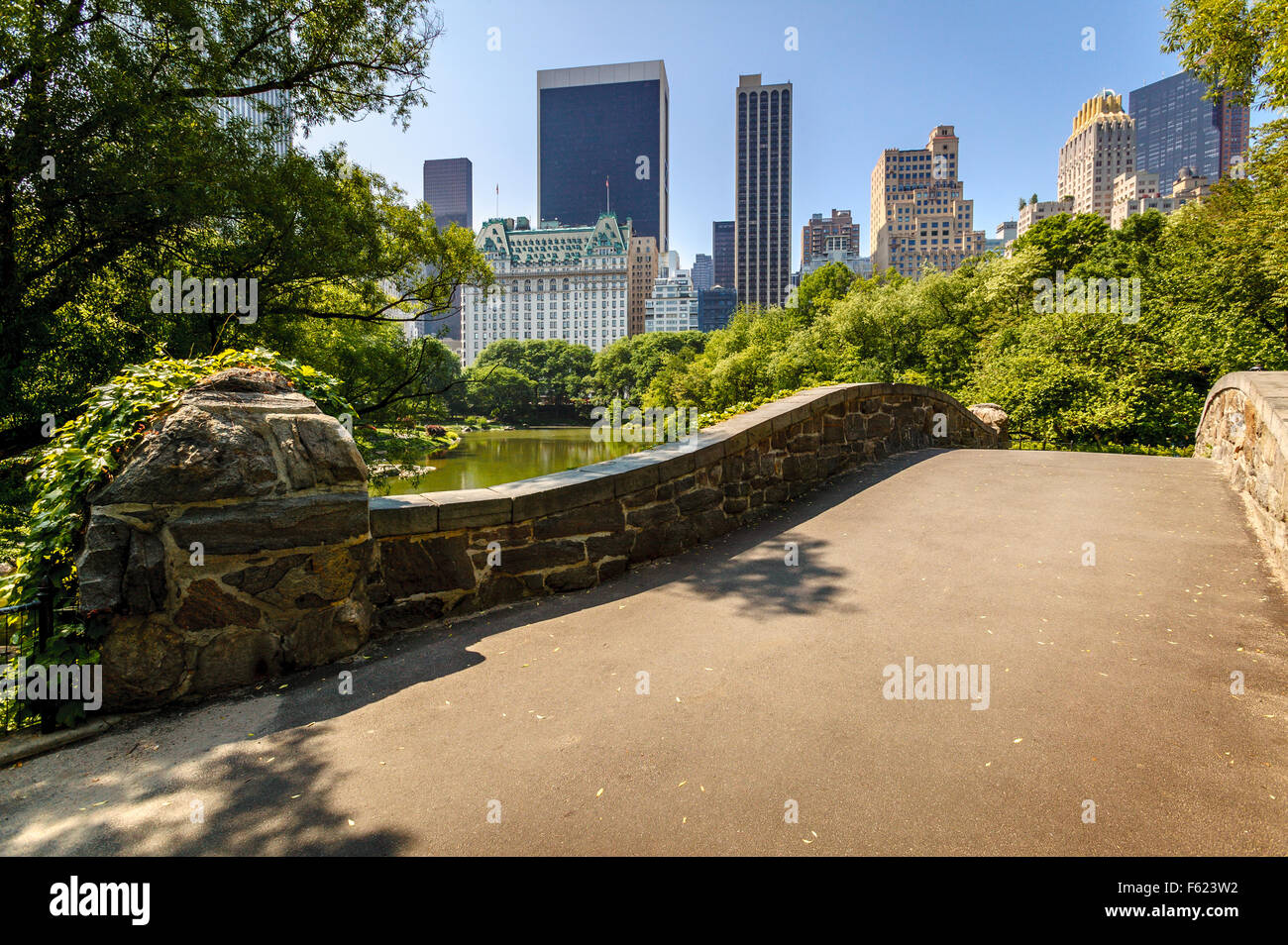 Gapstow Bridge and The Pond on a Spring morning with view of Manhattan skyscrapers,  Central Park, New York City - Stock Image