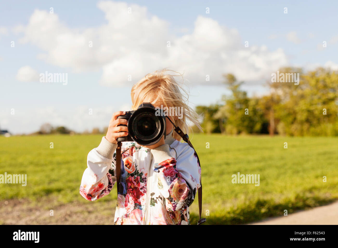 Girl photographing through SLR camera on field against sky Stock Photo