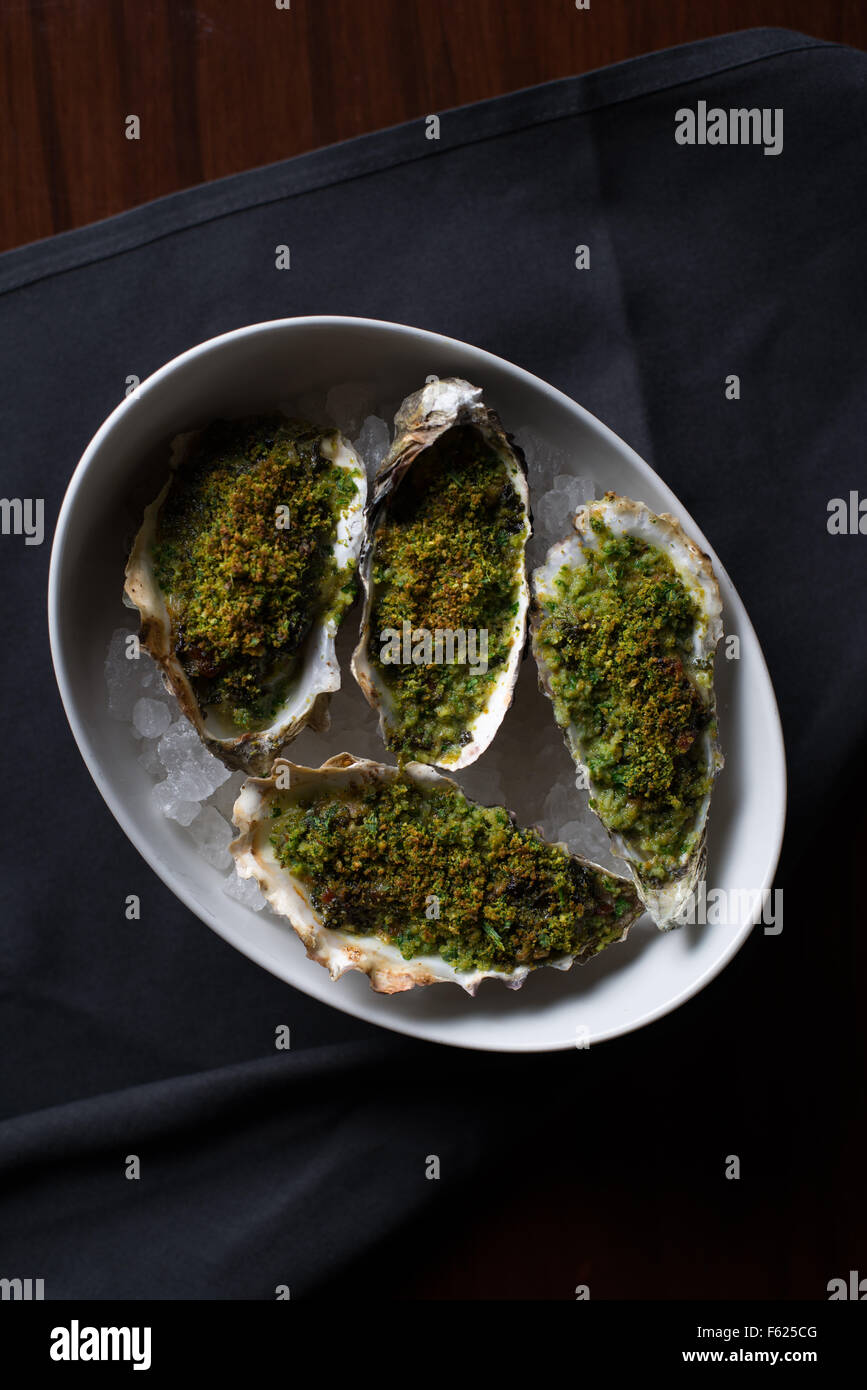 Overhead view of half-shell oysters made in the traditional rockefeller style. - Stock Image