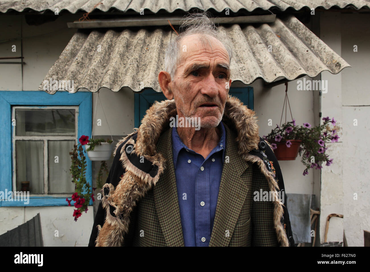 The returnee Ivan Ilchenko (82) in front of his house in the village Kupovate, located in the Chernobyl Exclusion - Stock Image