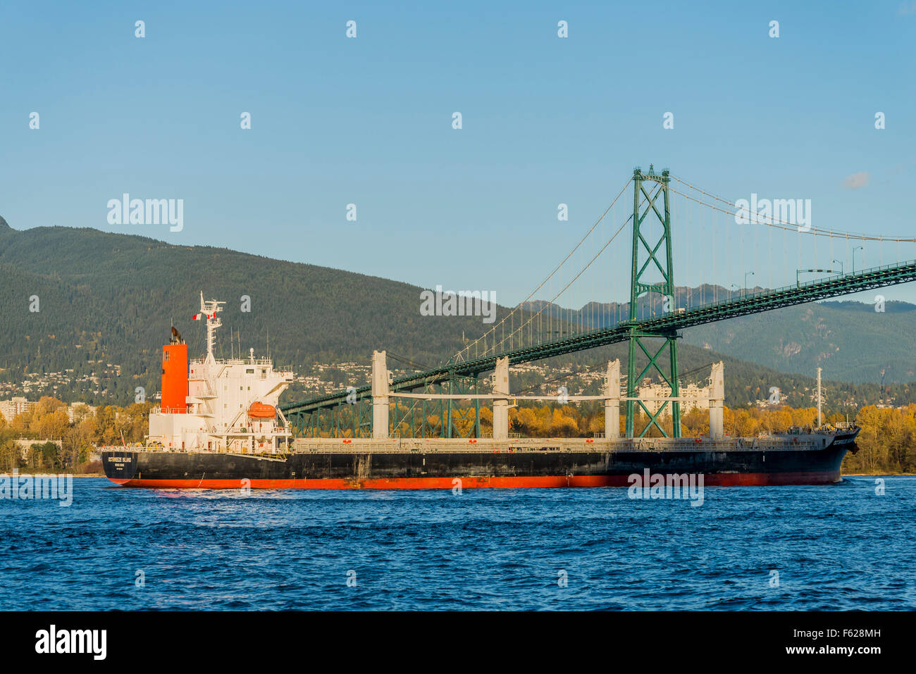 General Cargo ship, Octbreeze Island, passes under Lions Gate Bridge,   Vancouver, British Columbia, Canada - Stock Image