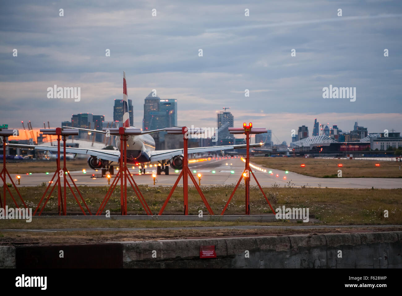 A passenger jet plane waiting to depart on the runway at London City Airport - Stock Image