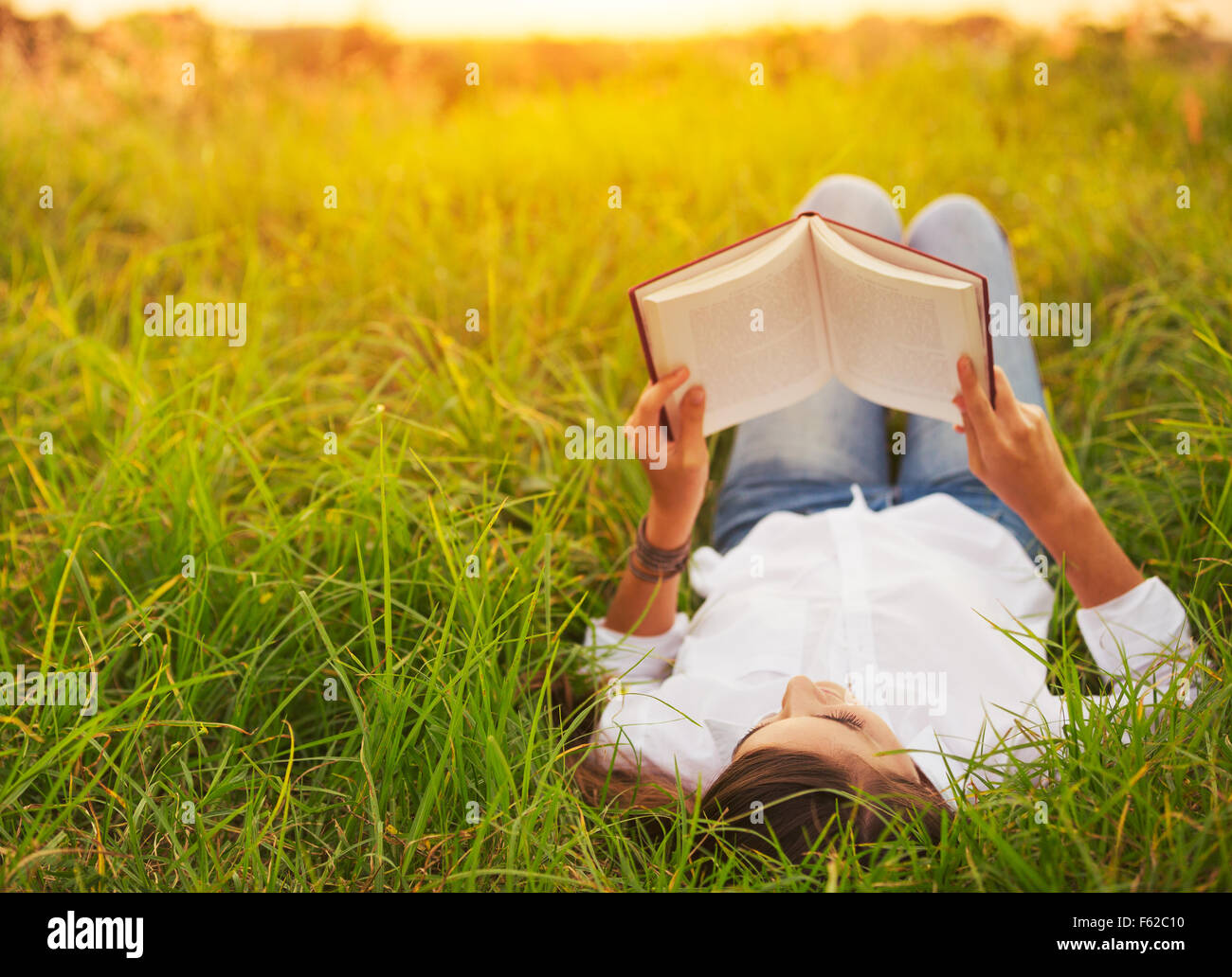 Young Woman Enjoying a Book Reading Outdoors - Stock Image