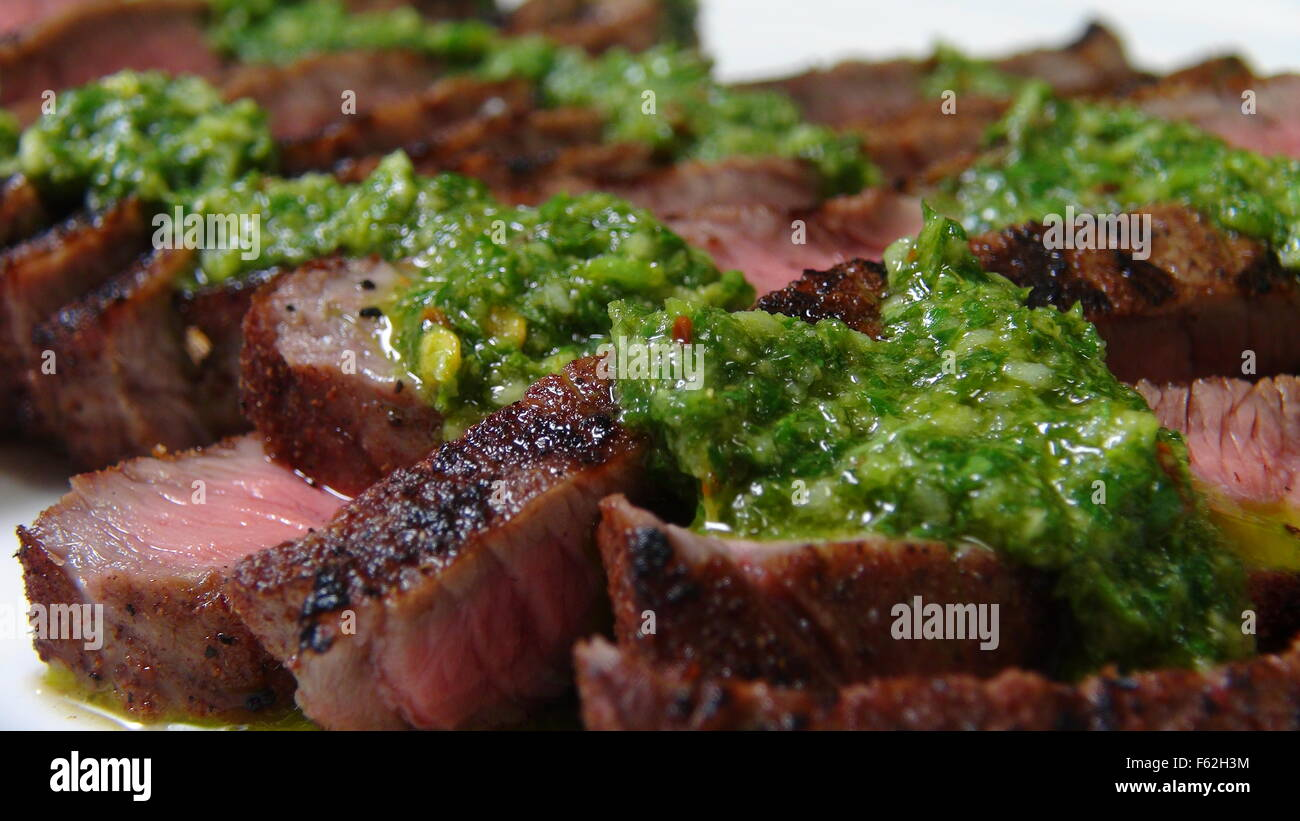 Grilled Sliced Steak and Chimichurri Sauce - Stock Image