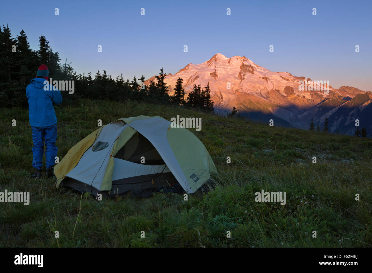 WASHINGTON - Backpacker at campsite on Liberty Cap watching the sunrise on Glacier Peak in Glacier Peak Wilderness. - Stock Image