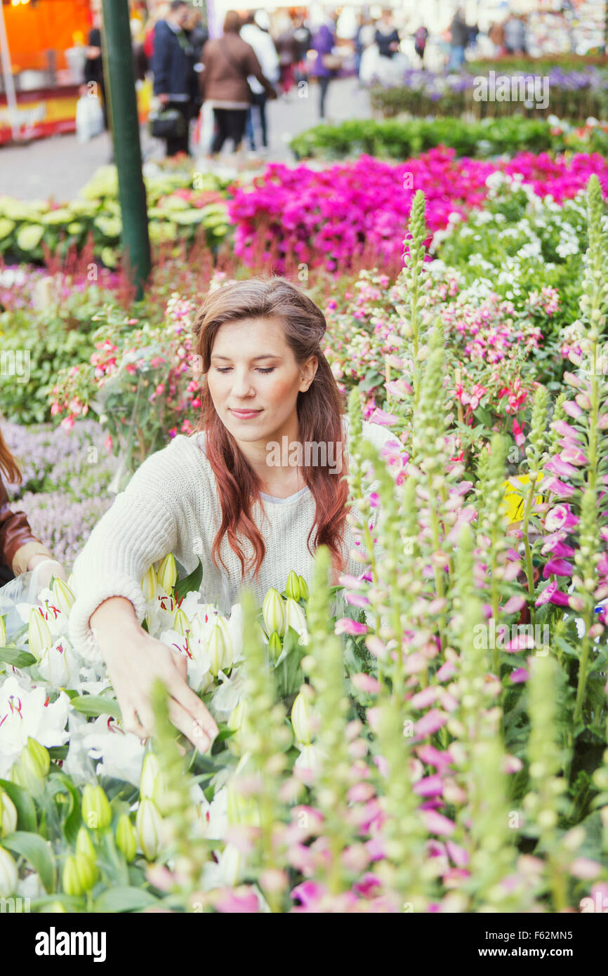 Young woman touching flower plants at market Stock Photo