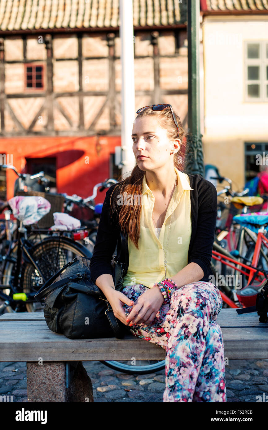 Beautiful woman sitting on bench at parking lot in city - Stock Image