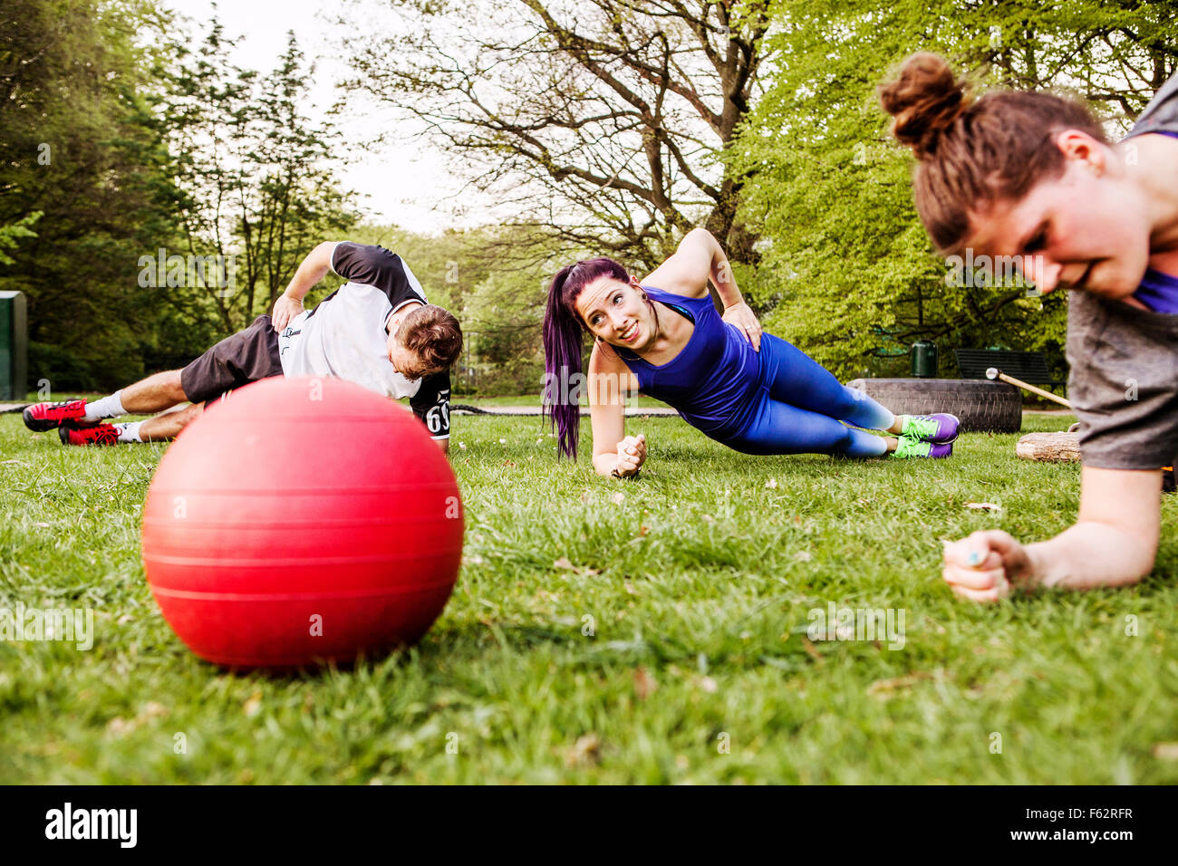 People doing side plank on grassy field at park - Stock Image