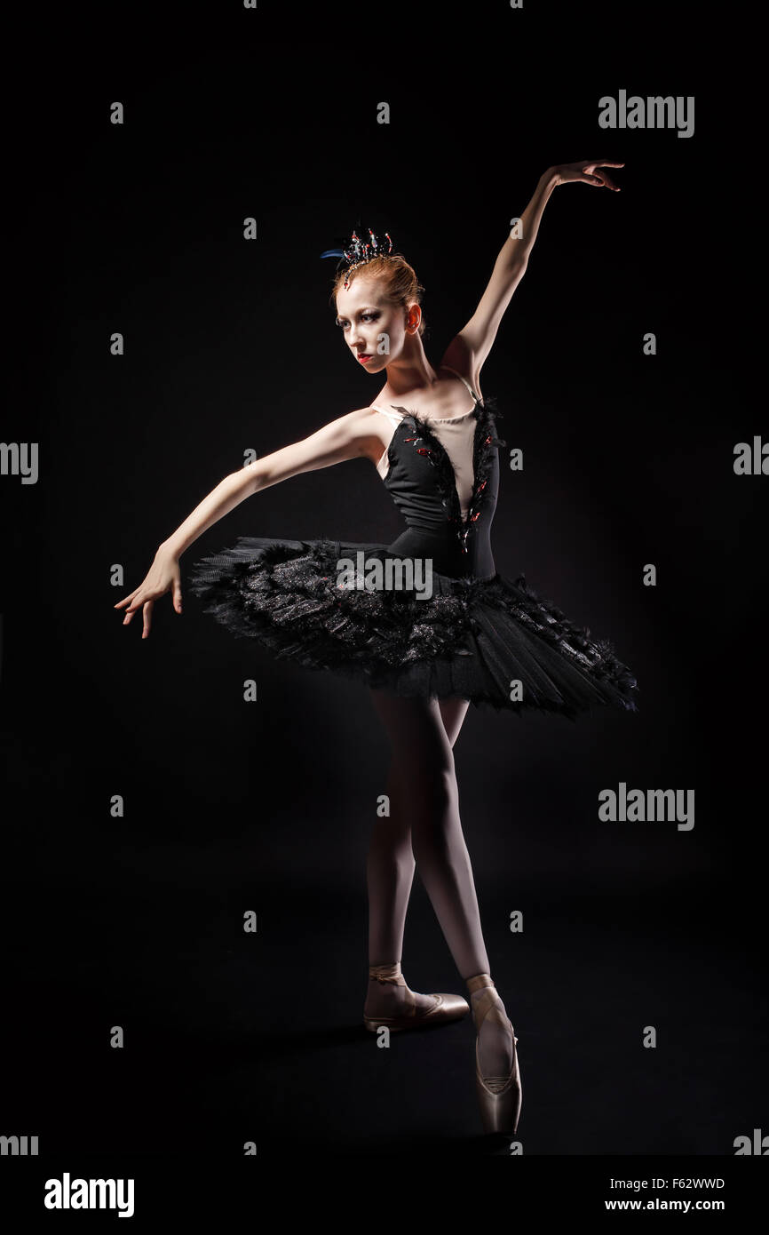 Slim ballerina in a black corset and black tutu. Rehearsal in the theater. Classical Ballet. Photography in low - Stock Image