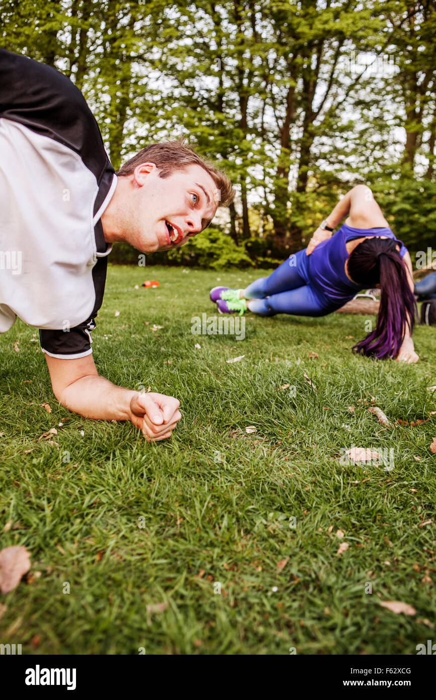 Man and woman doing side plank on grassy field at park - Stock Image