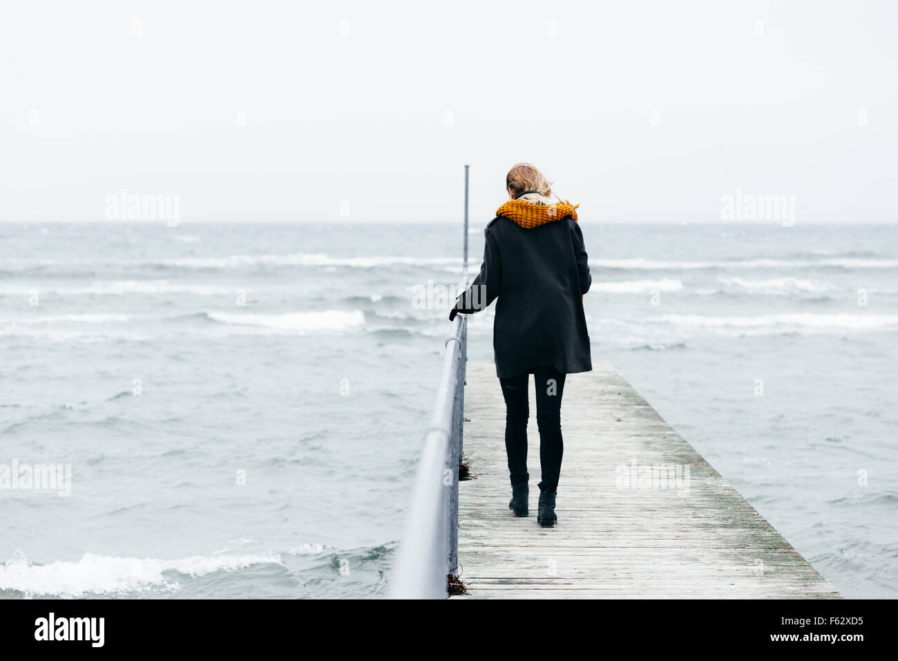 Full length rear view of woman walking on pier over sea - Stock Image