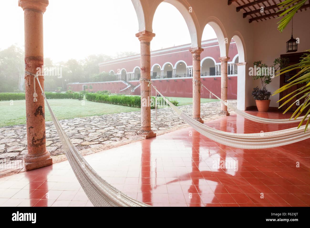 Hammocks line the patio on a misty morning at the Temozon hacienda in Yucatan, Mexico. - Stock Image