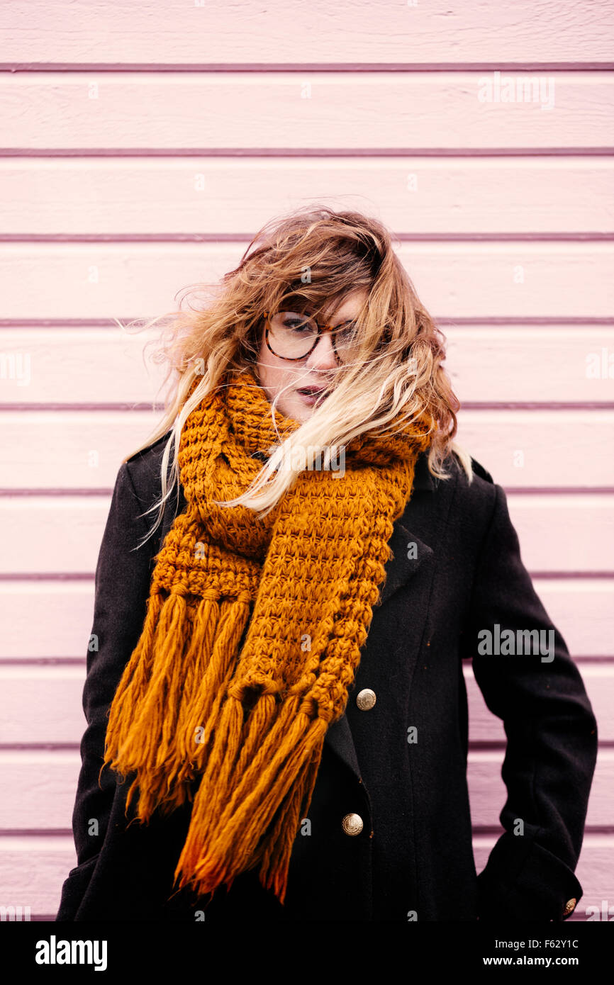 Portrait of young woman wearing scarf while standing against wooden wall - Stock Image