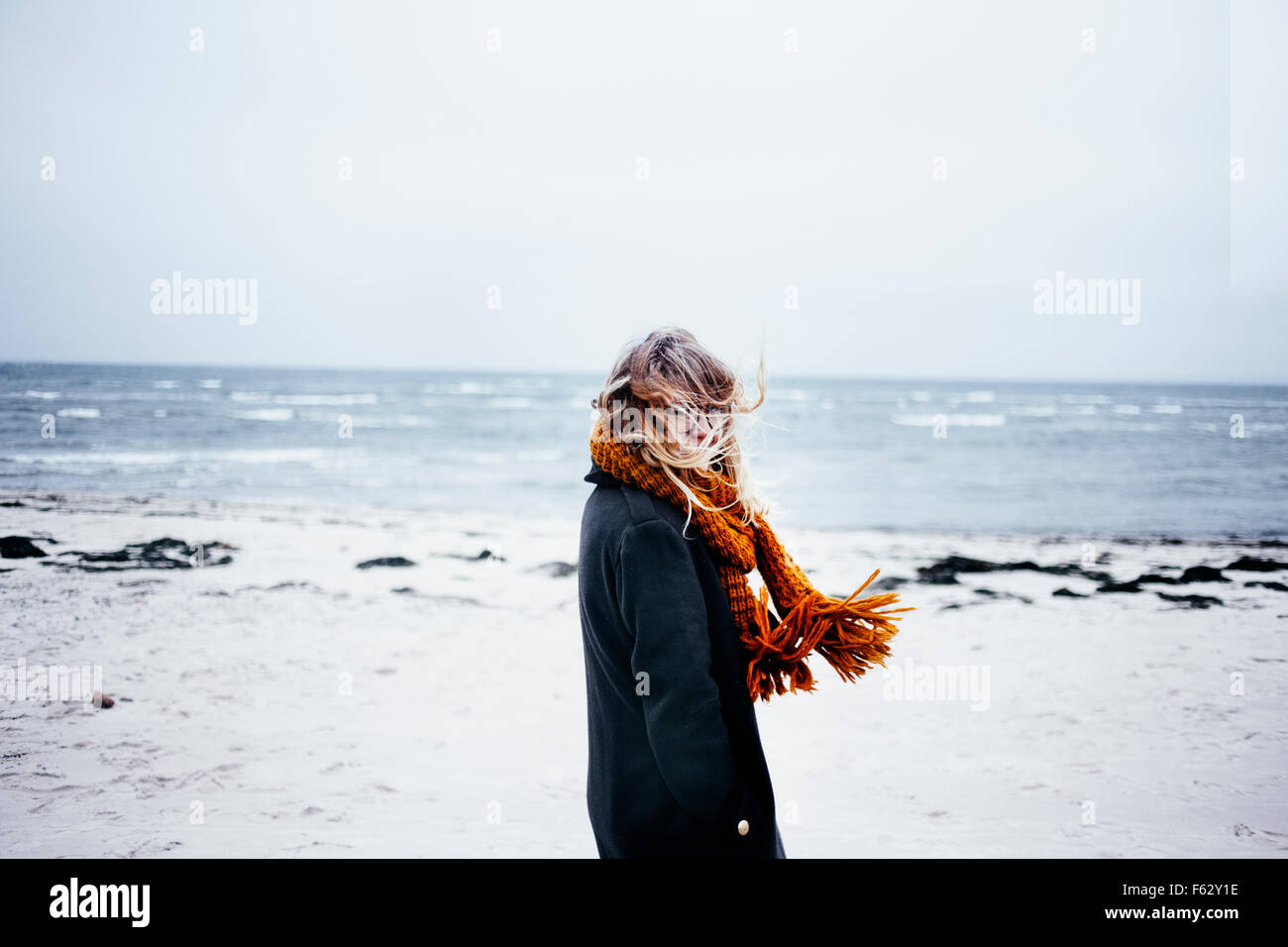 Side view portrait of young woman wearing scarf at beach - Stock Image