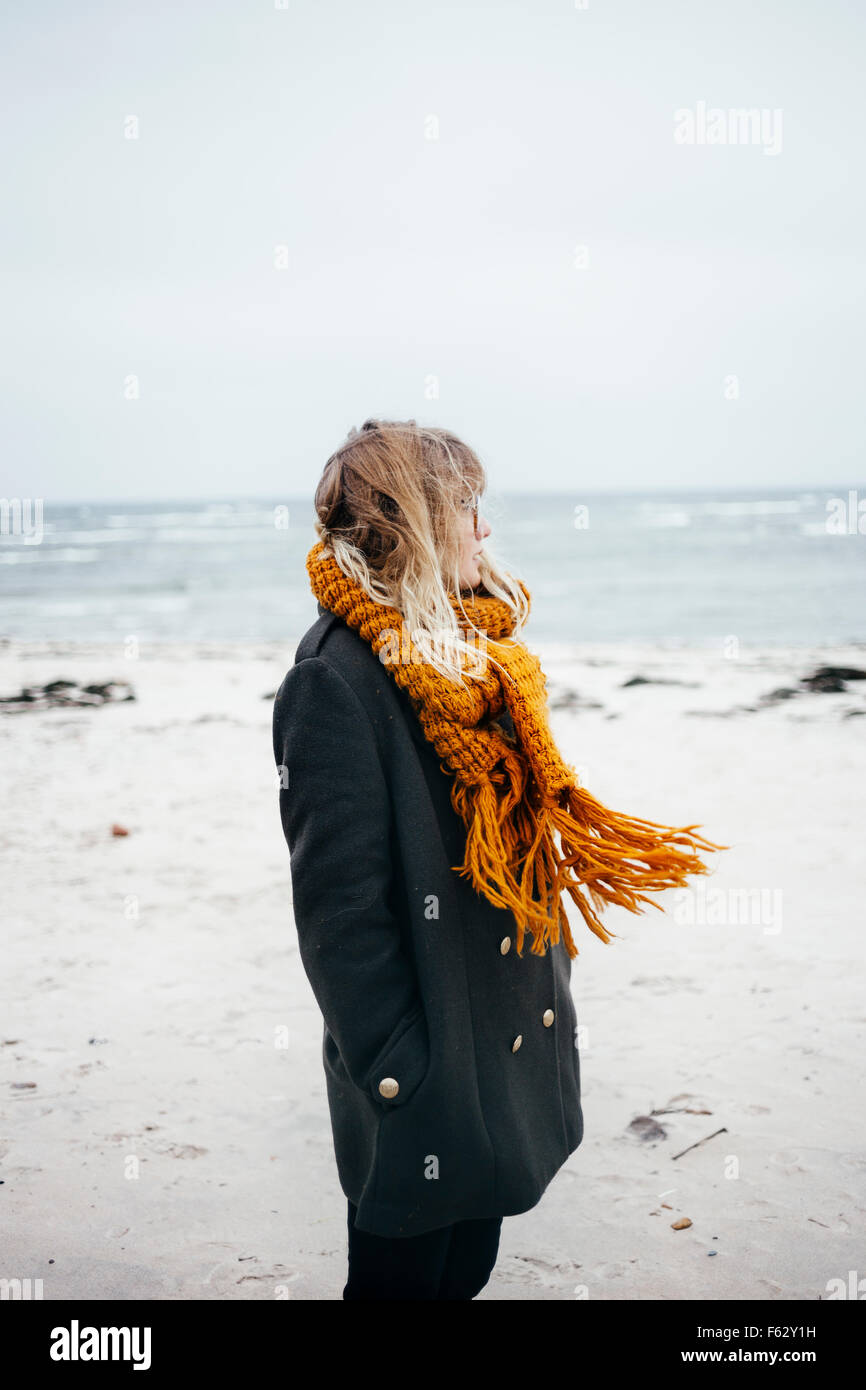 Side view of young woman wearing scarf while looking away at beach - Stock Image