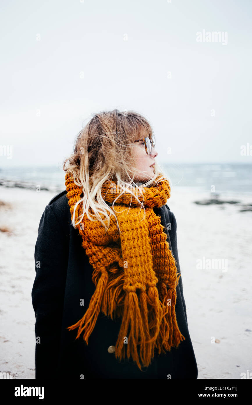 Young woman wearing scarf while looking away at beach - Stock Image