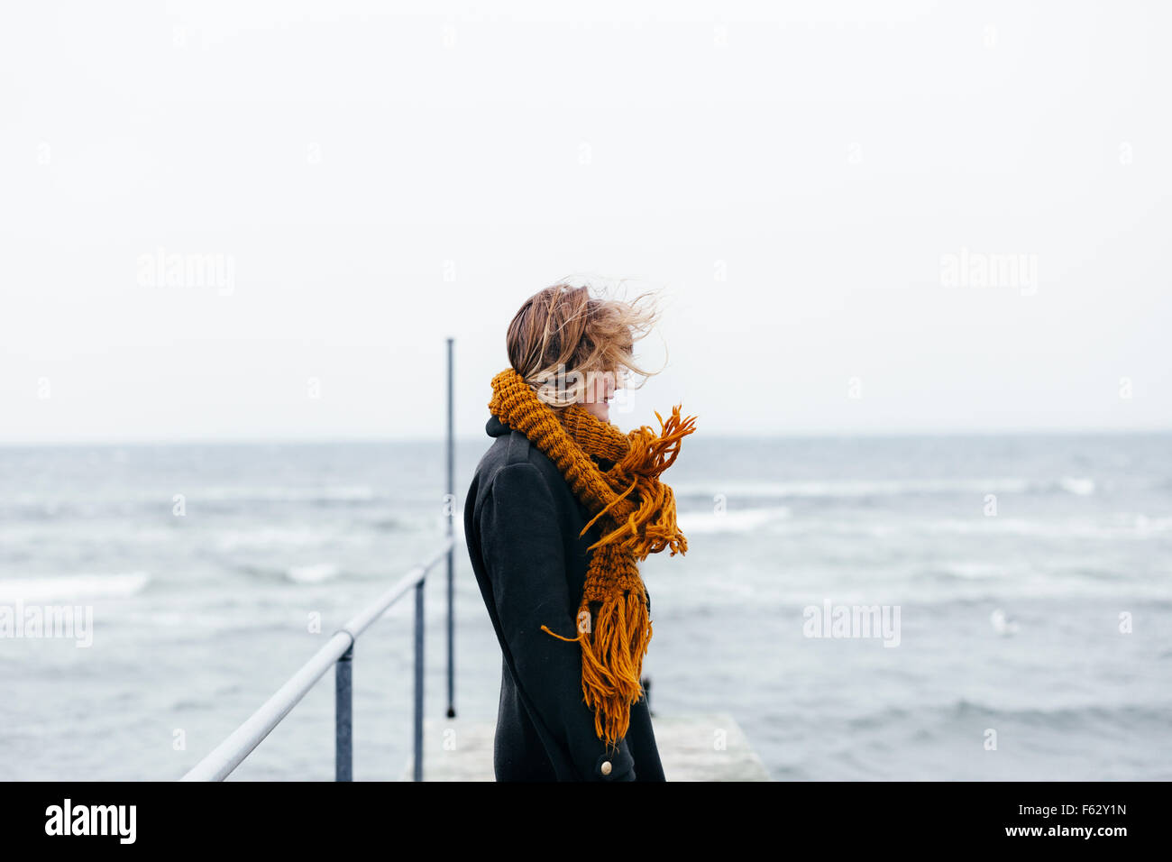 Side view of young woman wearing scarf standing on pier over sea - Stock Image
