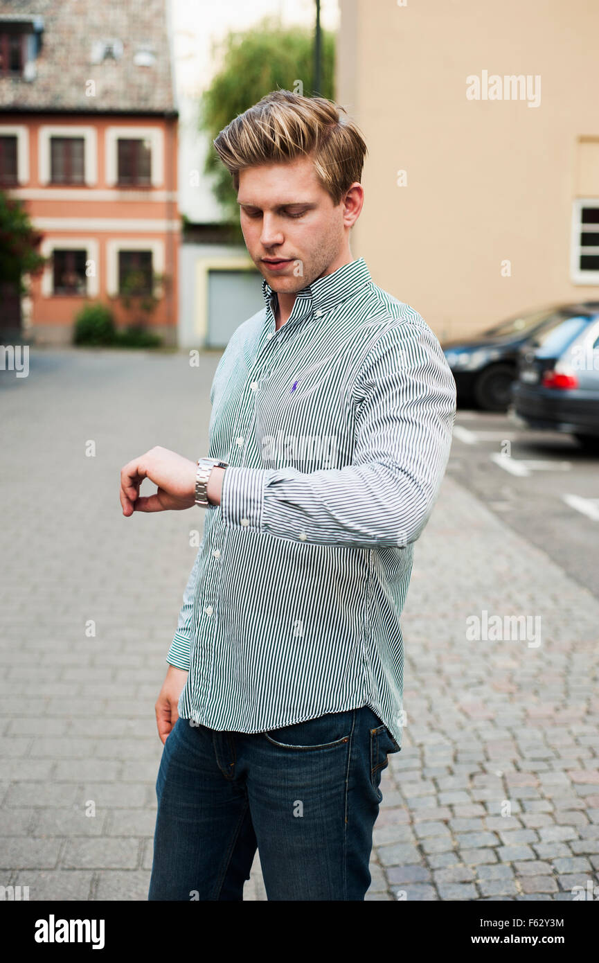 Handsome man checking time while standing on street in city - Stock Image