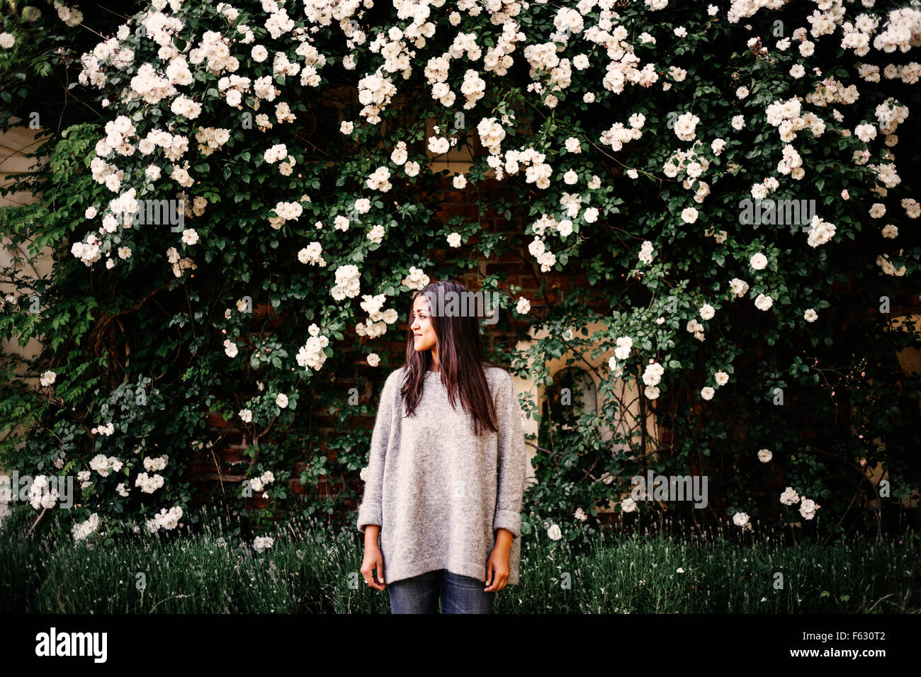 Young woman standing against tree bearing white flowers in park - Stock Image
