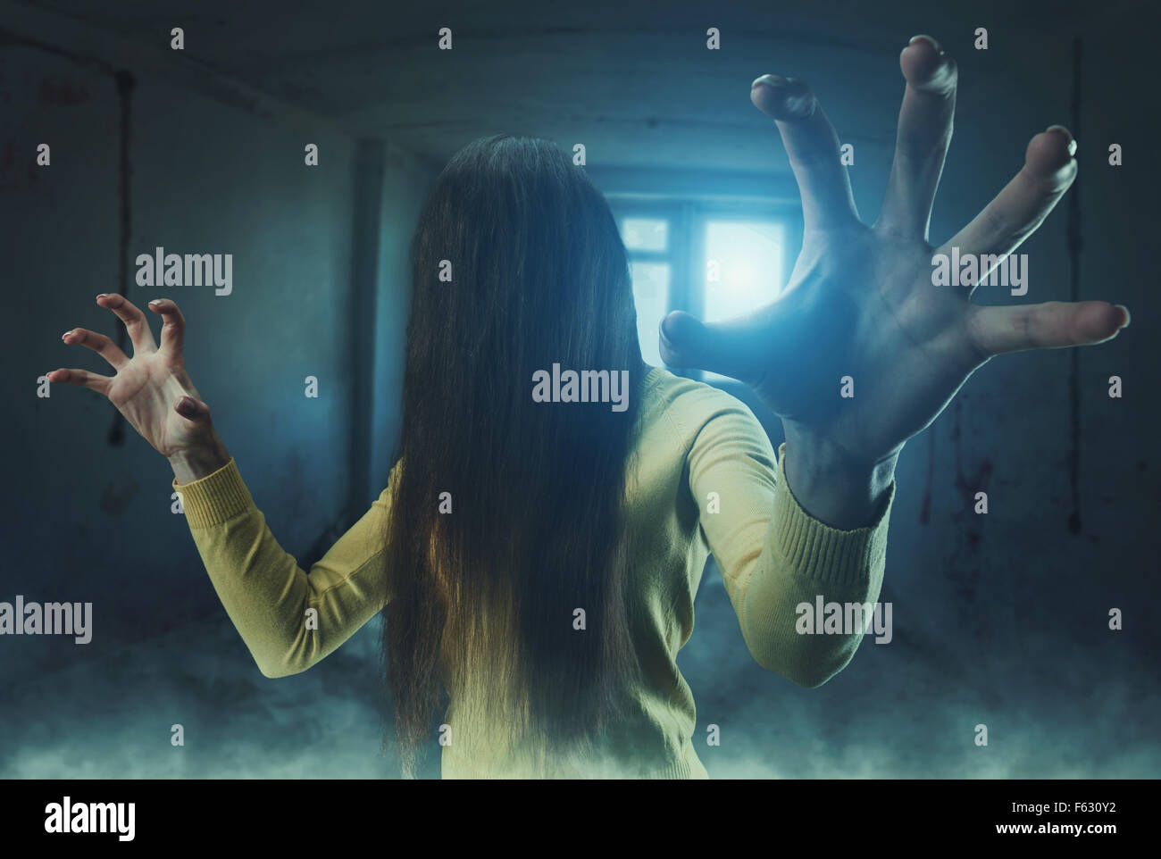 Zombie girl with long hair in her face in an abandoned building - Stock Image