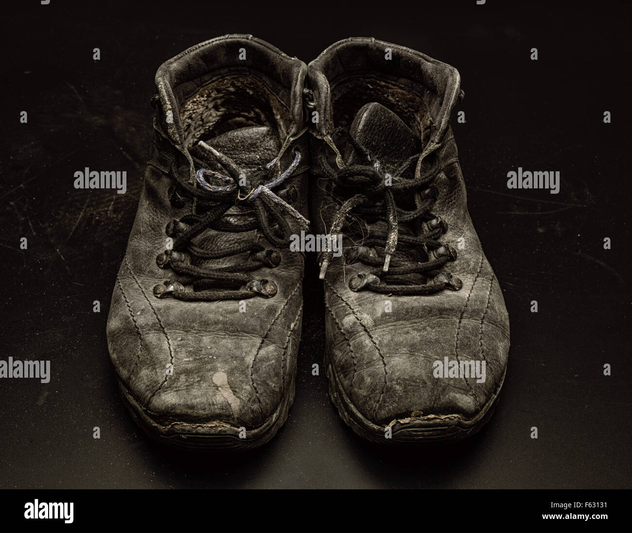 Old worn out shoes on the black floor - Stock Image