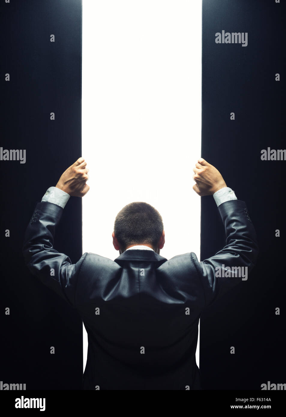 Businessman opening the gate to a bright light - Stock Image