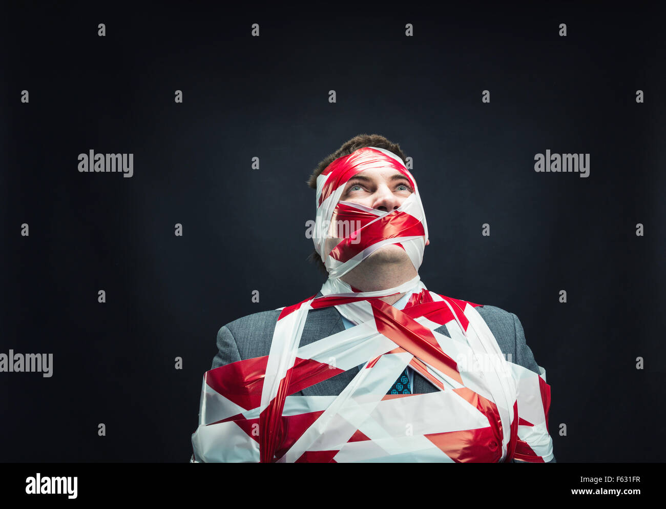 Victum man with stripped  red and white duct tape over body - Stock Image