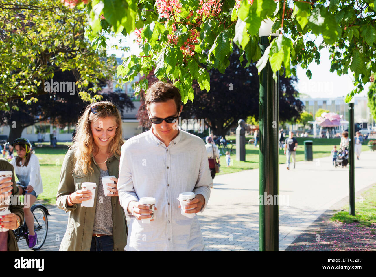 Couple holding disposable cups while walking on street at park - Stock Image