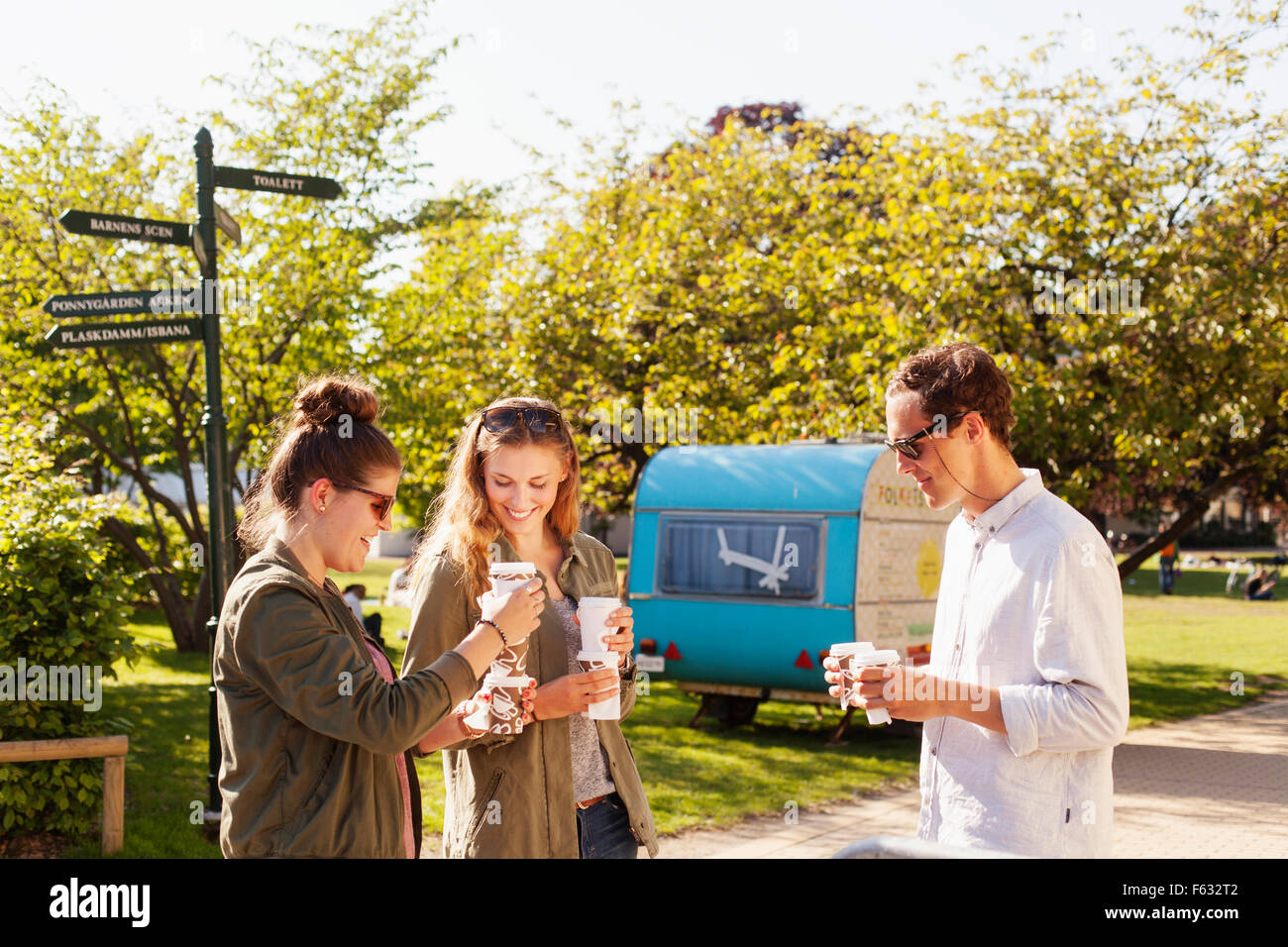 Happy friends holding disposable cups while standing at park - Stock Image