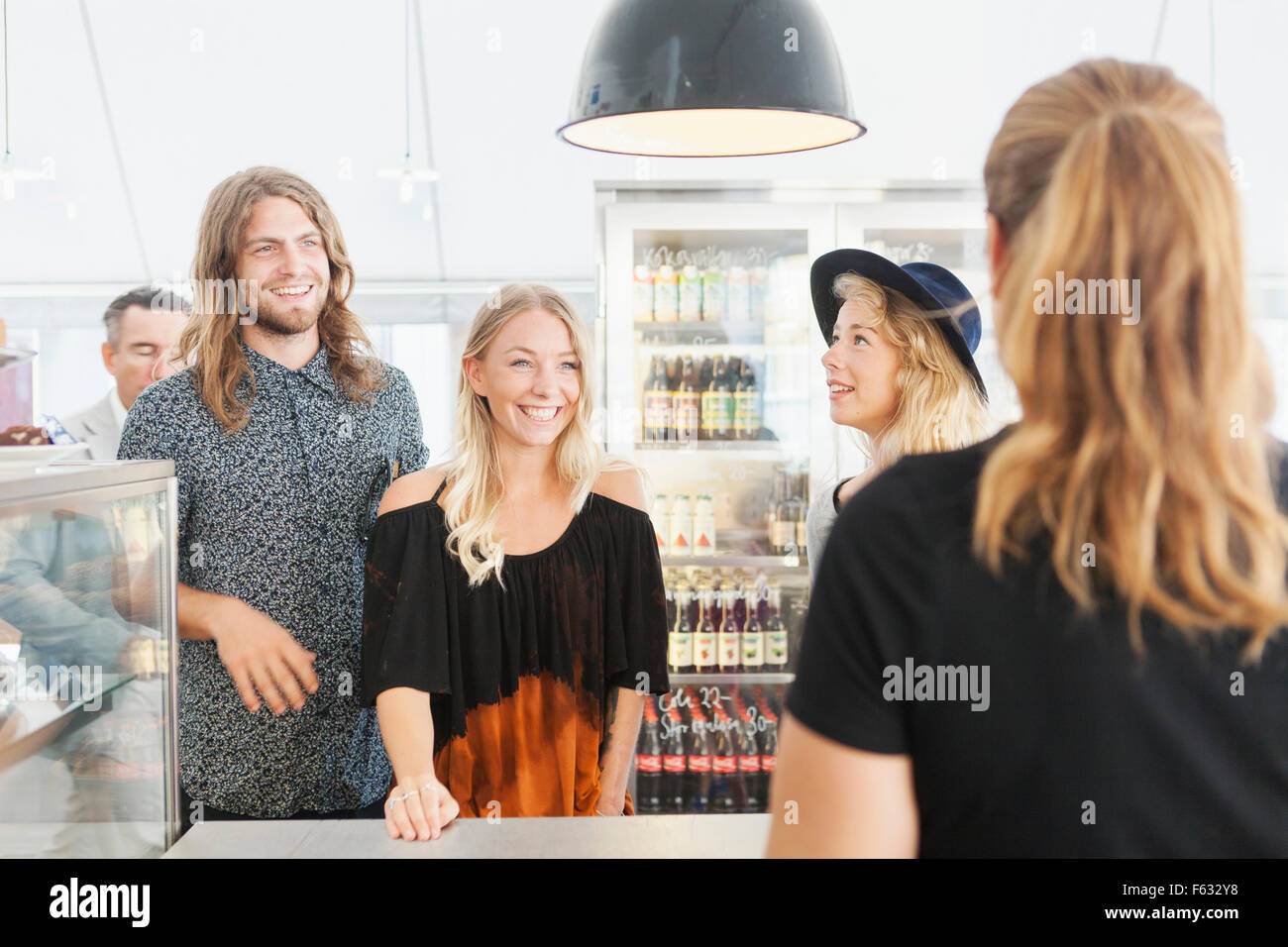 Happy friends talking to worker standing at restaurant counter - Stock Image