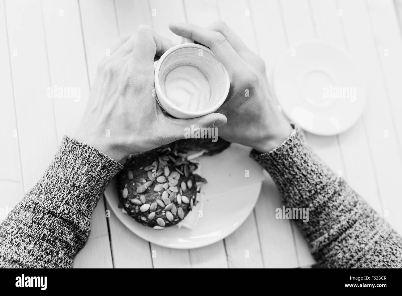 High angle view of man's hands holding coffee cup at cafe table - Stock Image