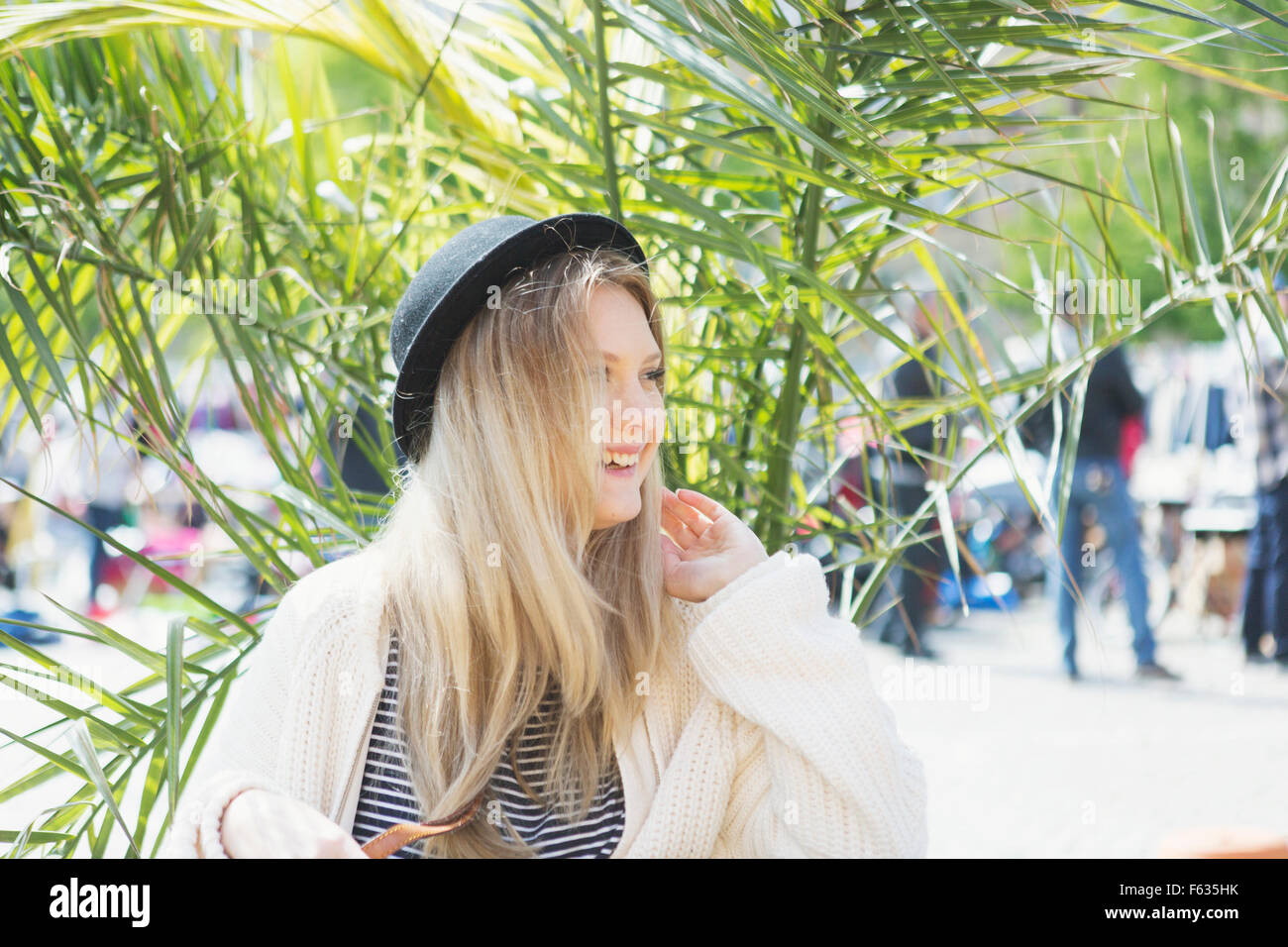 Beautiful smiling young woman sitting at cafe against plant - Stock Image