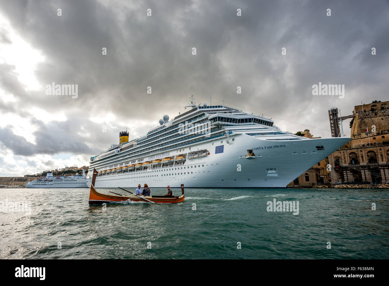 A traditional Maltese boat passes in front of a cruise liner in Valletta Harbour, Malta. - Stock Image