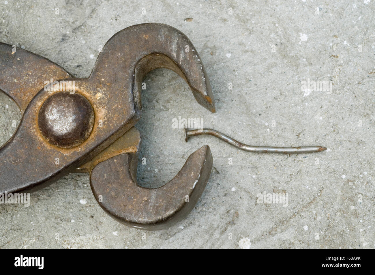 rusty tongs and nail on concrete background - Stock Image