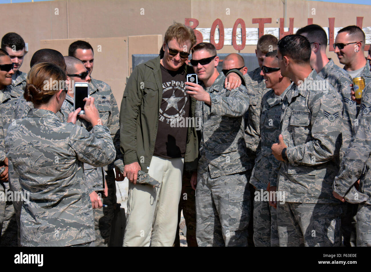 Late night talk show host and comedian Conan O'Brien poses for photos with U.S. airmen during a visit to the - Stock Image
