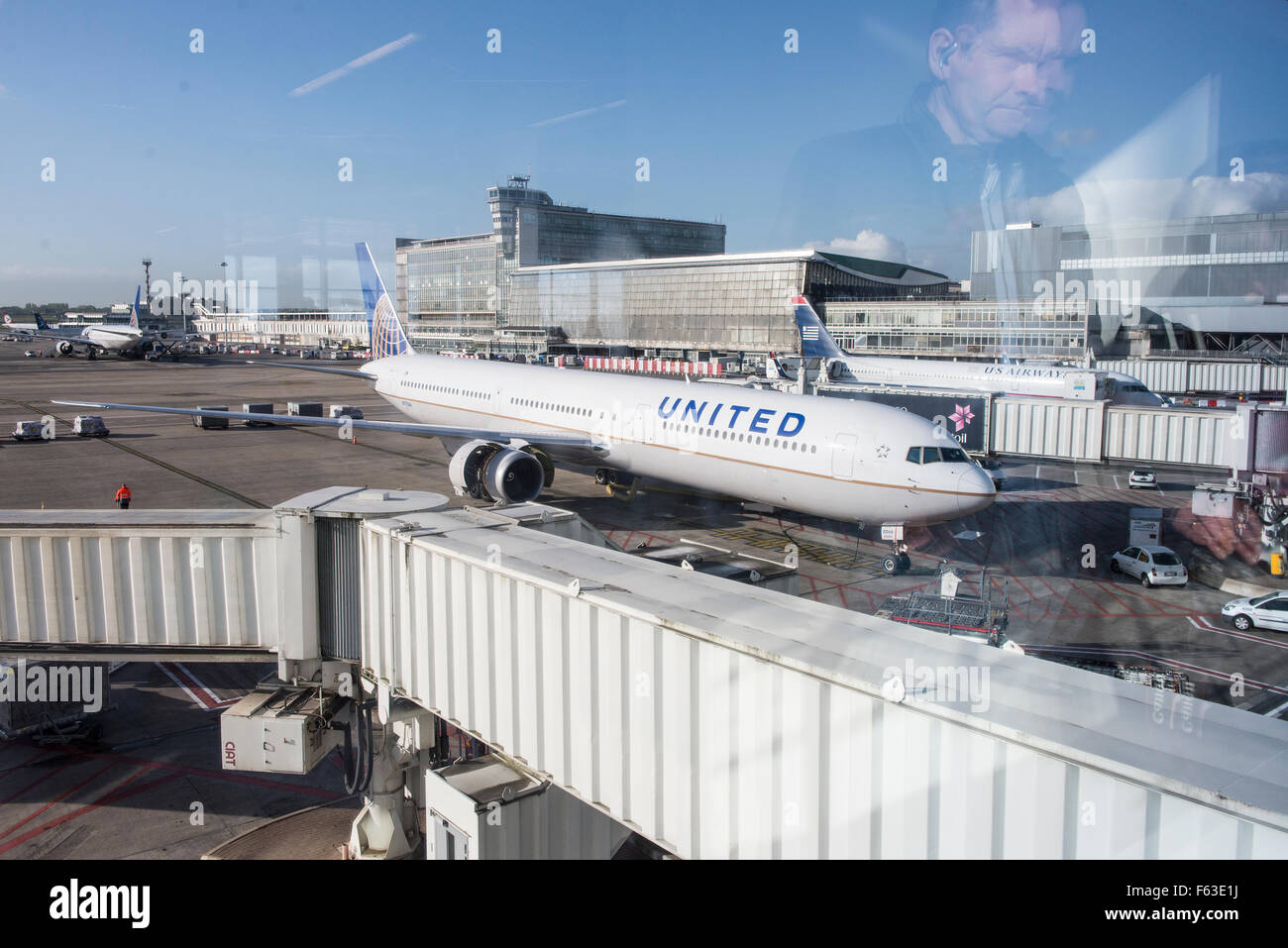 Man looking through terminal window to airplane Boeing 767-424(ER) with registration N77066 of United Airlines at - Stock Image