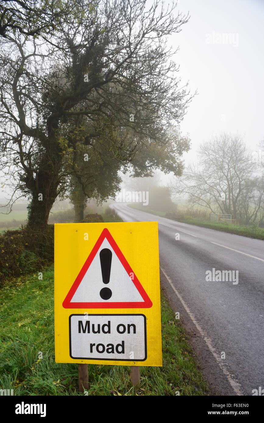 mud on road ahead warning sign in fog yorkshire united kingdom Stock Photo