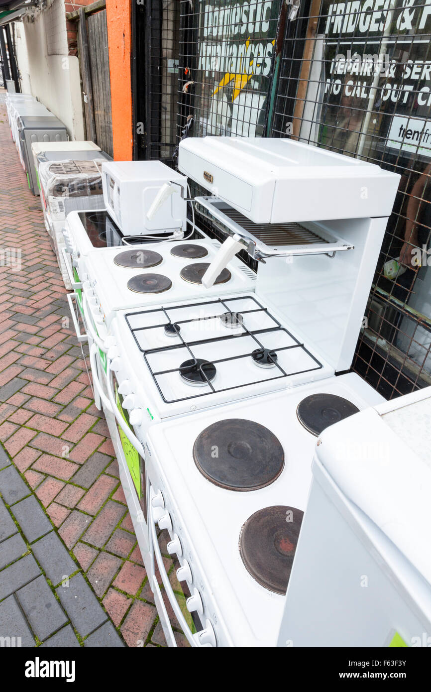 Second hand cookers, old white goods and other used domestic appliances for sale outside a shop on a UK town centre - Stock Image