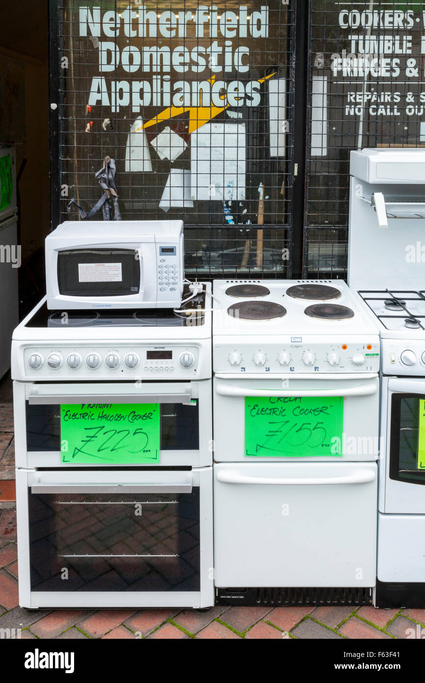 Shop selling second hand cookers, old domestic appliances and other used white goods on a high street in a UK town - Stock Image