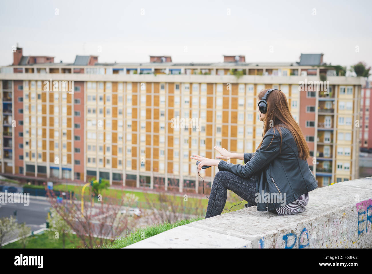 Young handsome eastern brunette girl listening music sitting on a small wall in the city suburbs, view from back - Stock Image