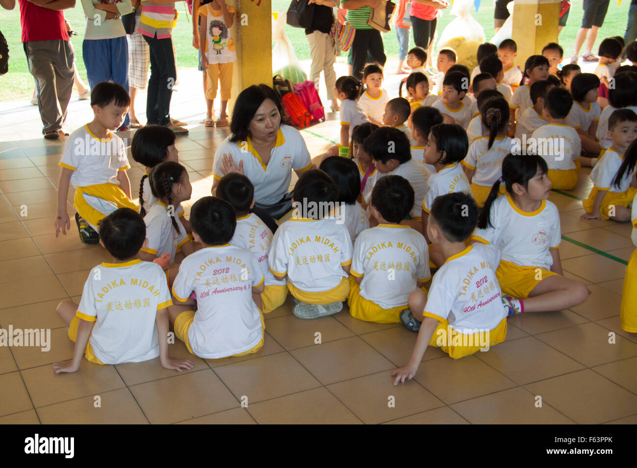 Teacher briefing the childrens on their sport day activity. - Stock Image